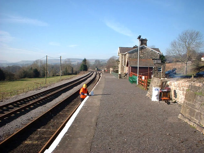 Painting the platform edge at Redmire Station - photo courtesy of Andrew Chapman, Wensleydale Railway Association