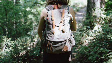 woman with a backpack walking in the woods following a walk fest route
