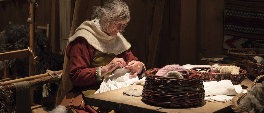 performance of a Viking woman making clothing
