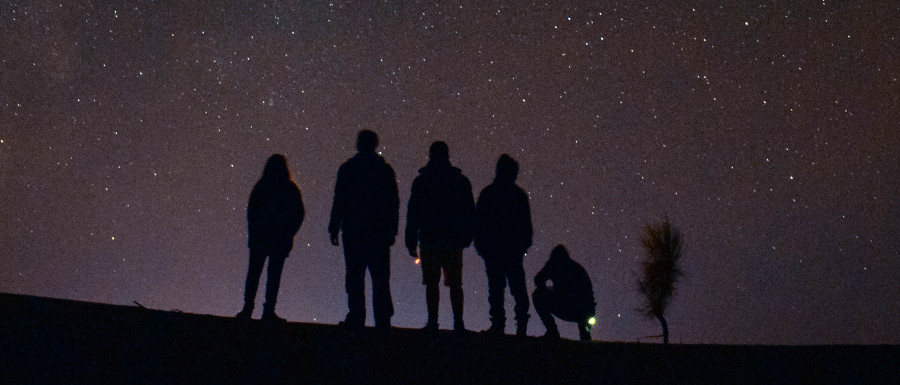 people looking at a star filled night sky