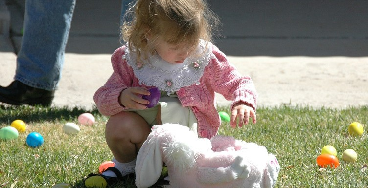 young child with an Easter basket surrounded by colourful eggs
