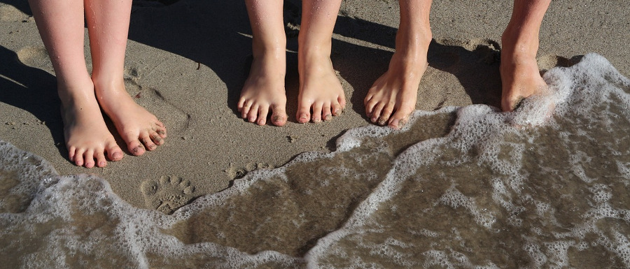 three pairs of feet in the sand and sea