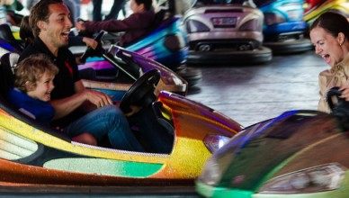 family using bumper cars at a fairground