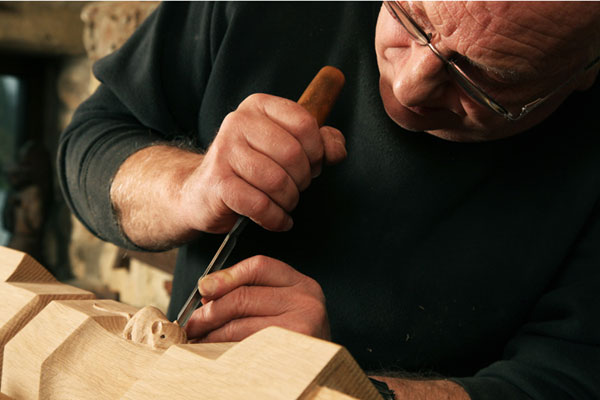 man carving a wooden mouse in one of the great Yorkshire museums